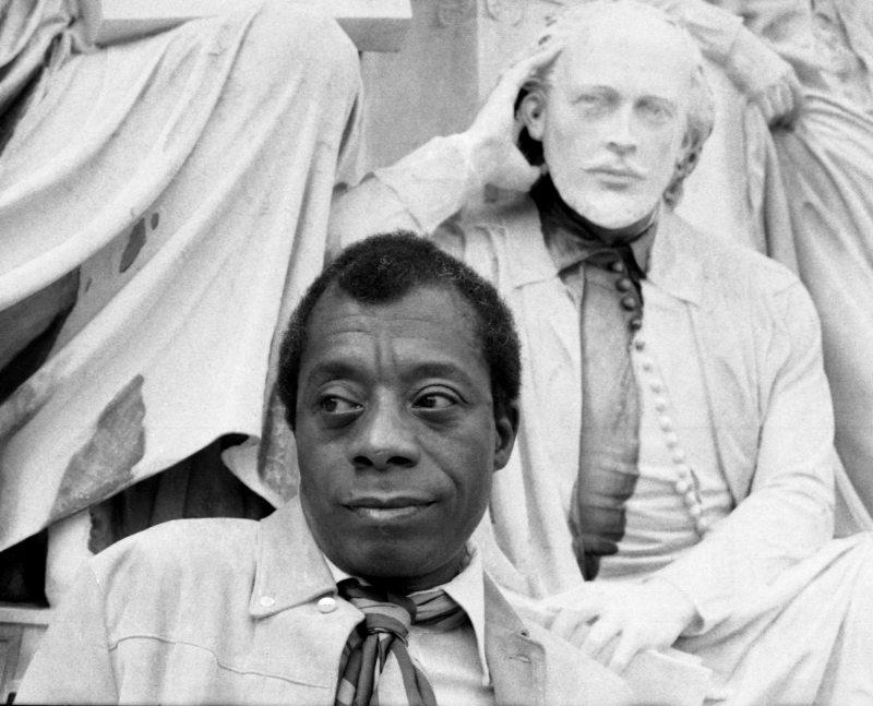 Author James Baldwin in front of a sculpture group with playwright William Shakespeare