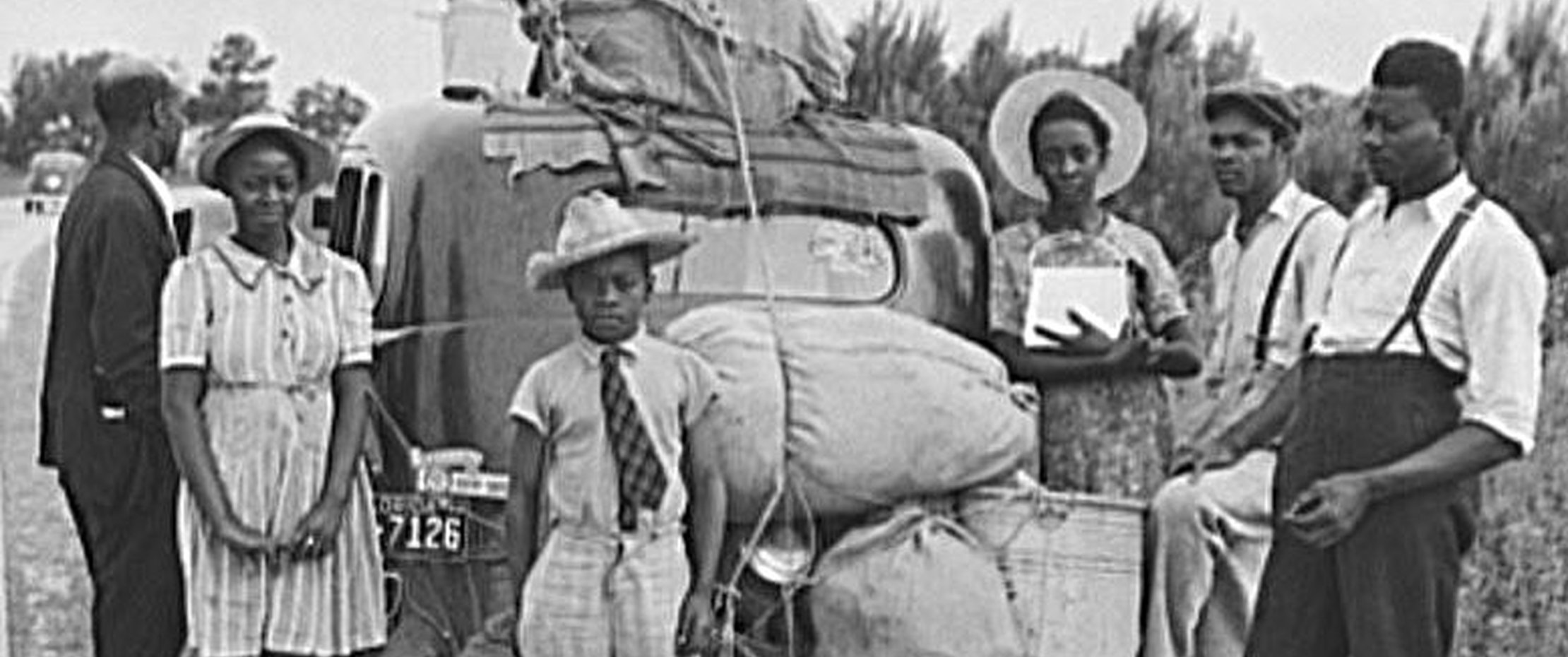 African American family in front of automobile with luggage piled on top