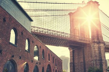 cityscape looking at Brooklyn Bridge from DUMBO, Brooklyn with morning sun appearing through arch of bridge
