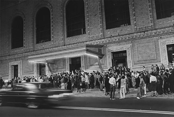 Exterior of a theater with a crowd on the street