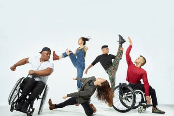 dance company on white stage featuring dance artists with a range of physical abilities