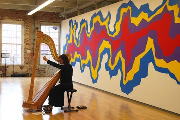 harpist in gallery with large-scale contemporary painting