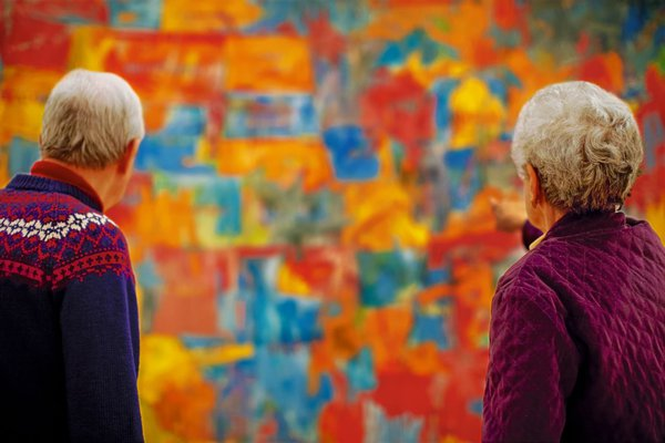 two elderly adults in front of an abstract painting