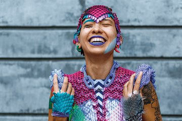 A Filipinx nonbinary person throws back their head and smiles joyously. They have tan skin and wear a reflective headpiece made of metallic scales.